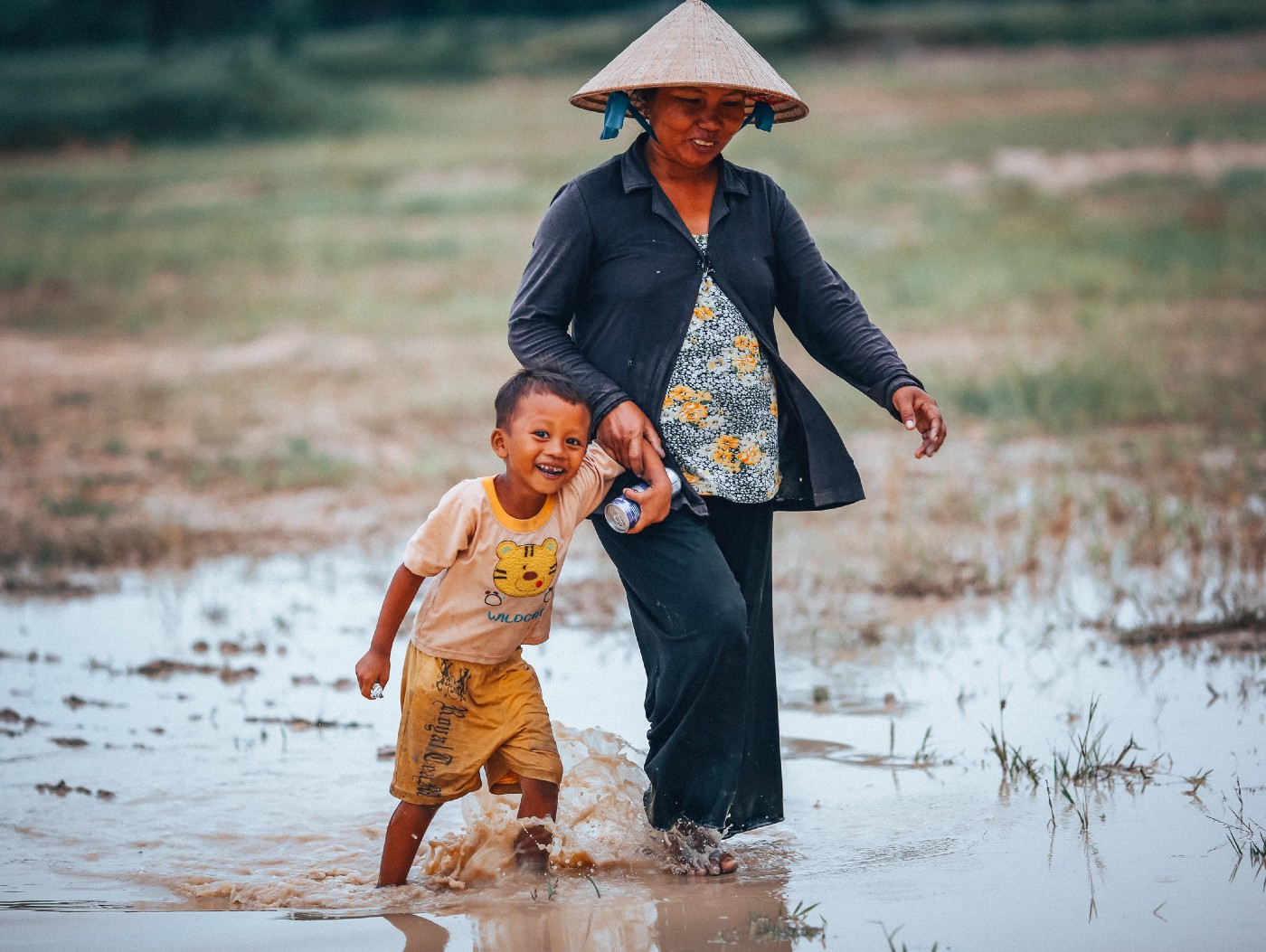 Asian woman and child walking through water.