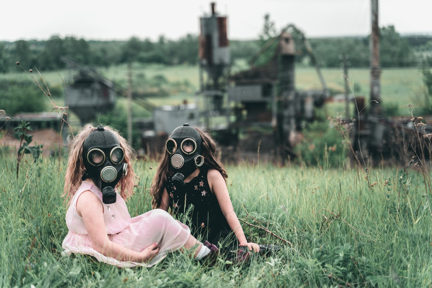 Two young girls sit on grass wearing gas masks.