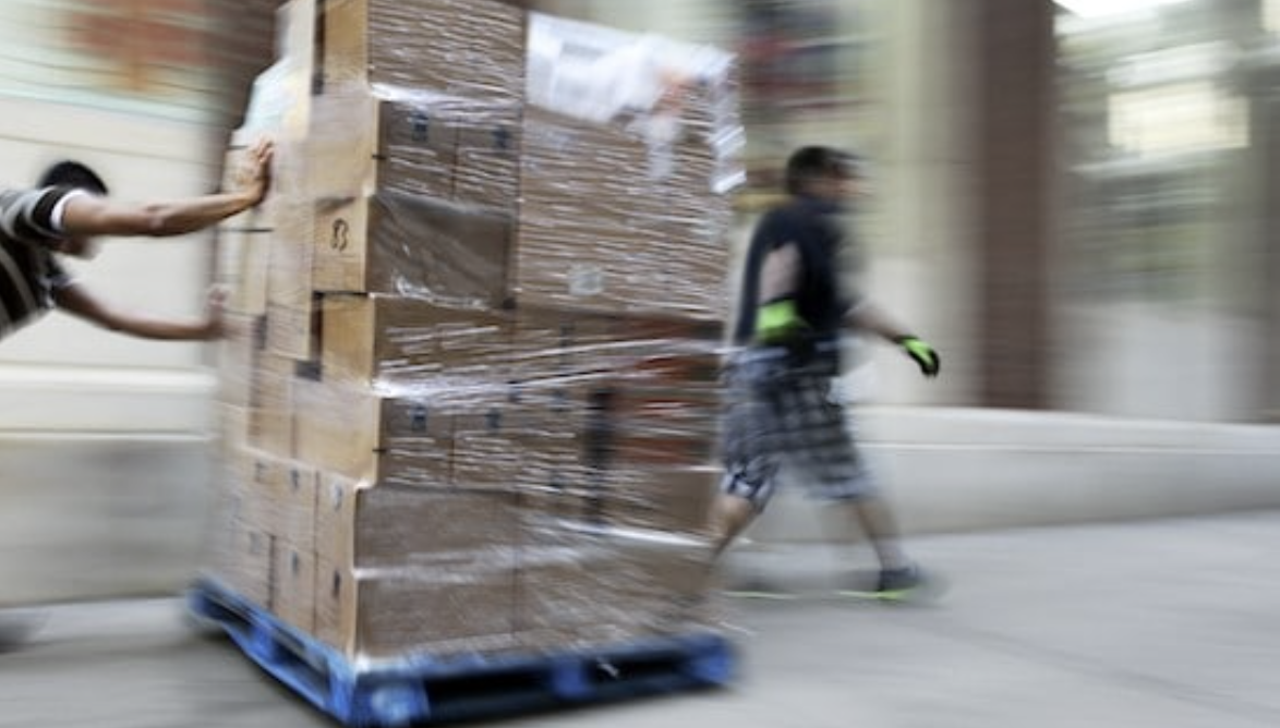Workers moving boxes in warehouse.