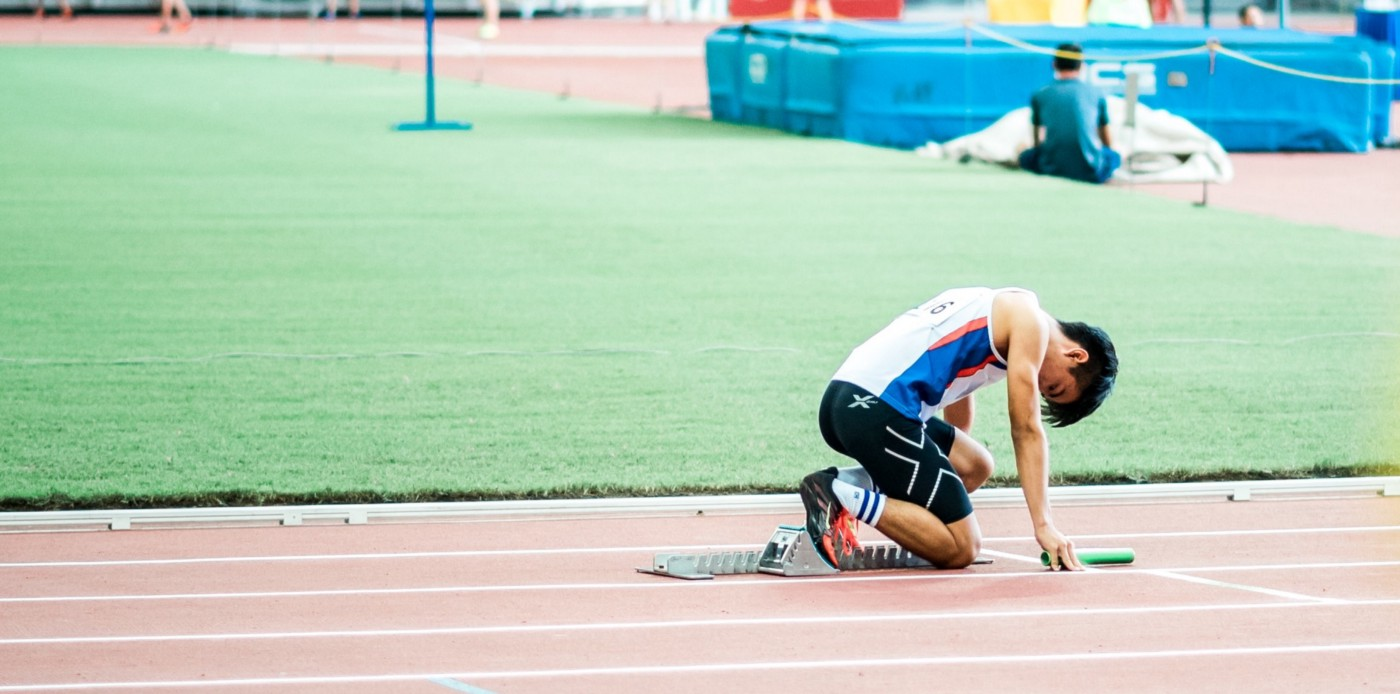 Runner crouches at the starting blocks