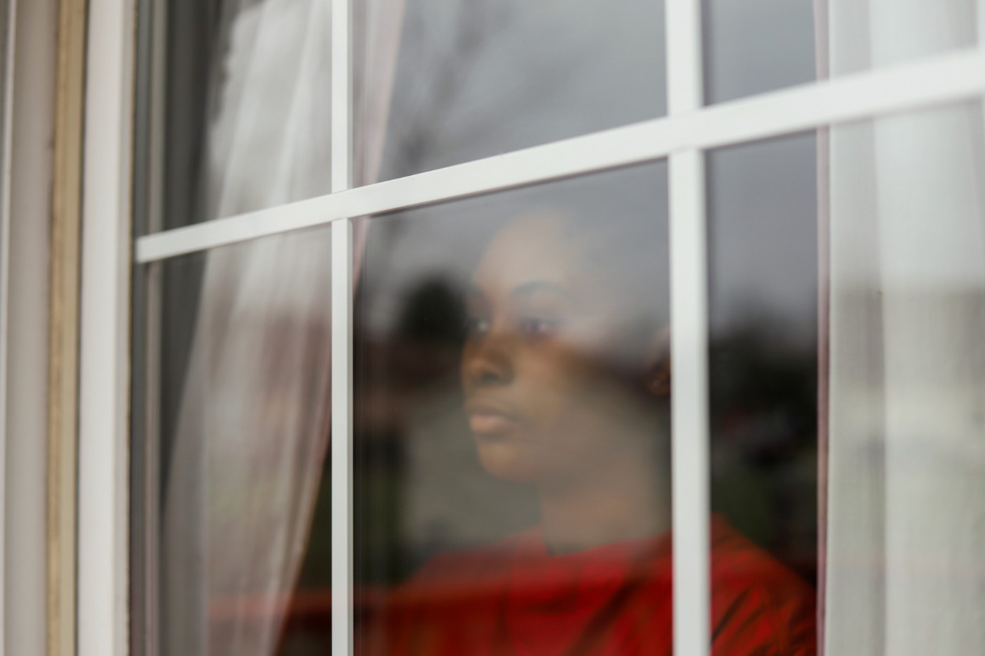Black woman looking out the window with a forlorn expression.