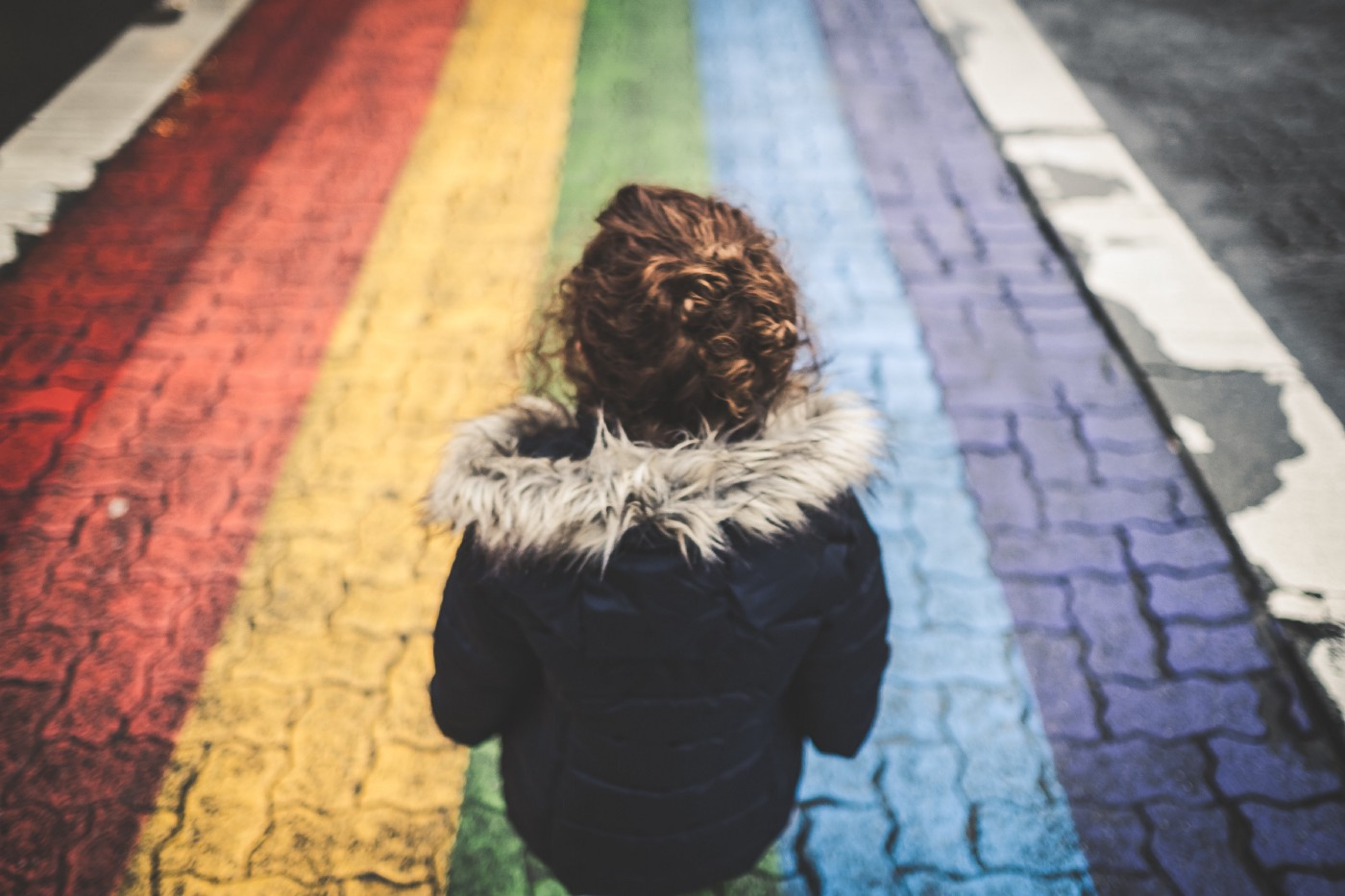 Child looking ahead at rainbow colored stripes on the road leading away from her