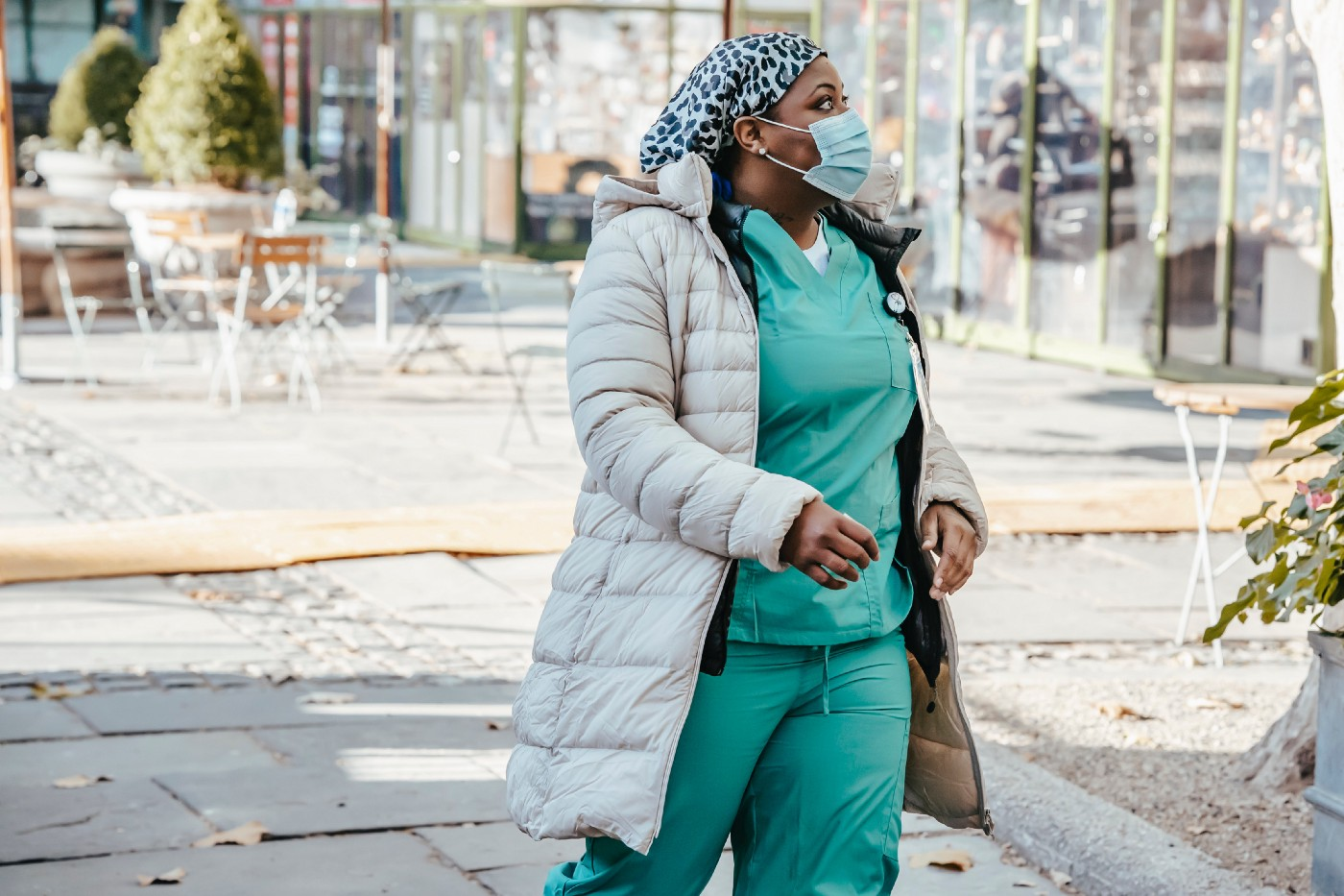 Woman in scrubs and mask walks through hospital courtyard