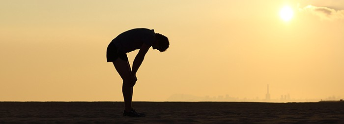 Silhouette of a man in shorts and a t-shirt. Sunset in the background. The man bends forward, hands resting on his knees. It looks like he has been for a run and is pretty exhausted now.