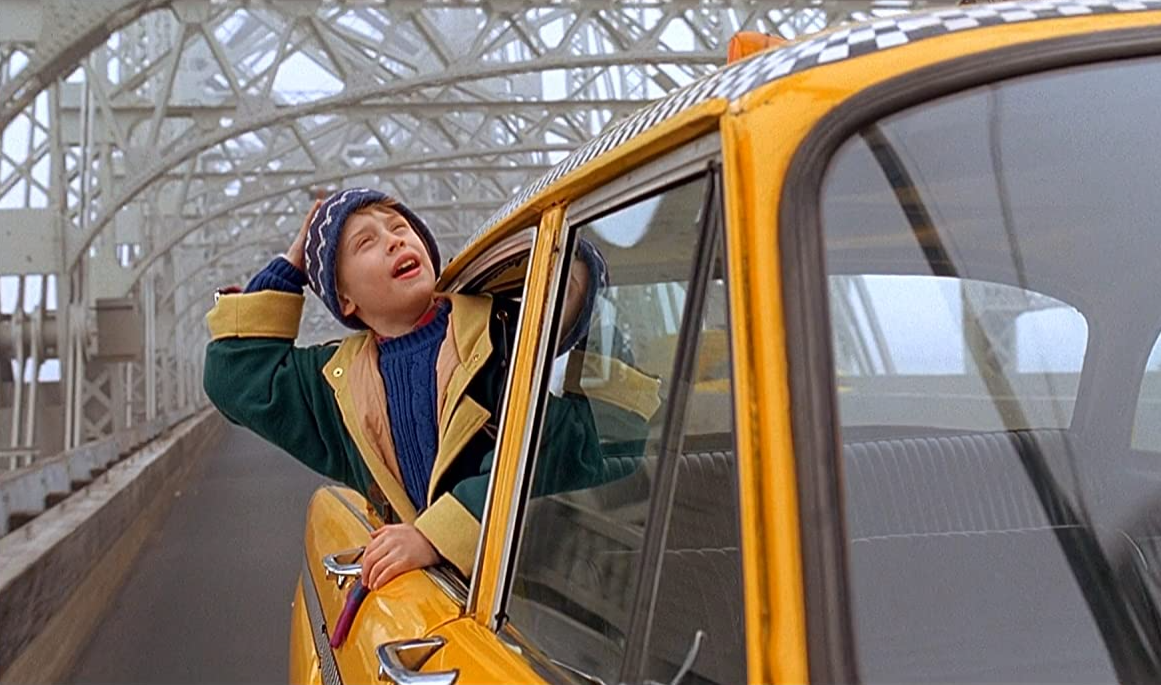 Still of Home Alone 2 where Kevin is riding in a yellow taxi down the Queensboro Bridge