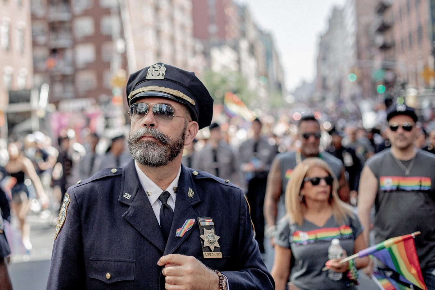 An aged man in police uniform in the middle of a Pride parade.