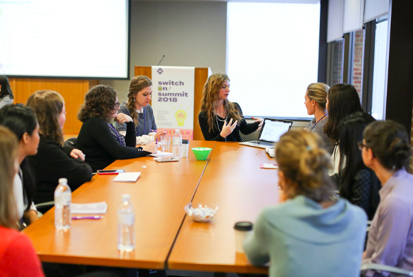 A group of women sitting around a table having a discussion at a tech conference.