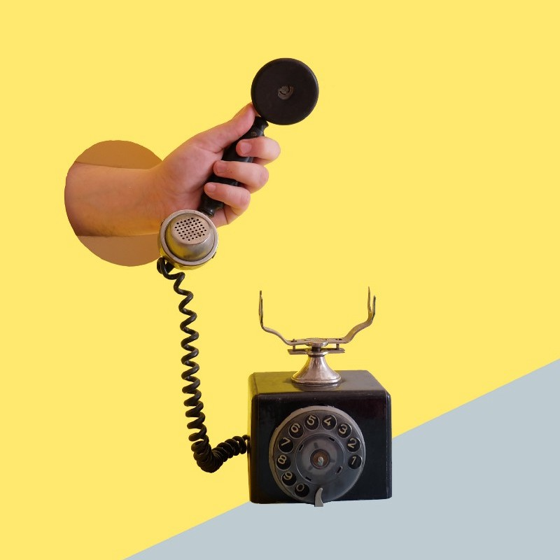 Analog rotary dial phone with a hand picking up the receiver