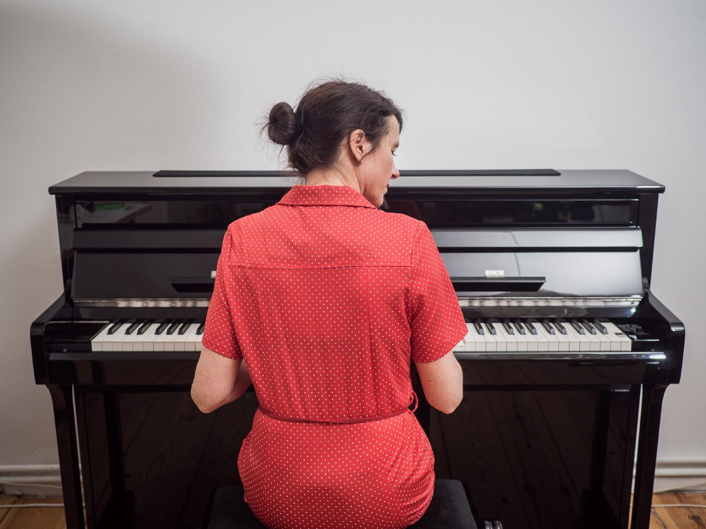 Rear view of a woman in a red dress playing the piano.