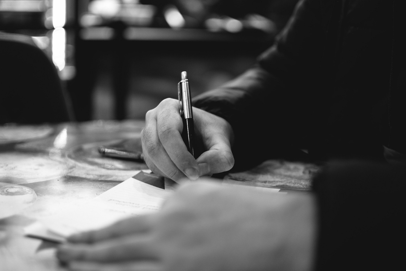 Man's hand on a notebook and table, in black-and-white.