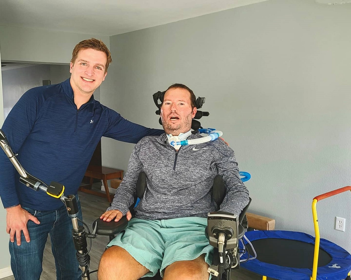 Man standing with another who is in a wheelchair.