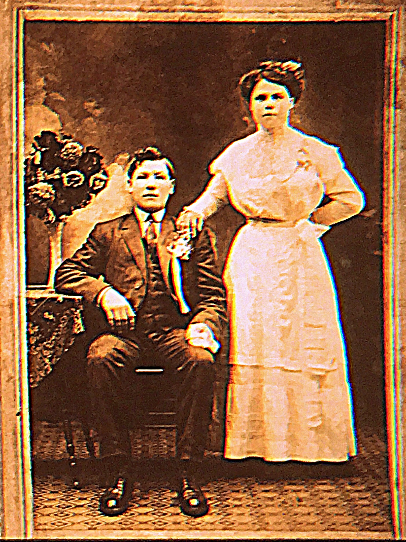 Antique photograph of a couple husband is seated and lady is standing wearing a very tight corset both very rigid looking posing for the camera