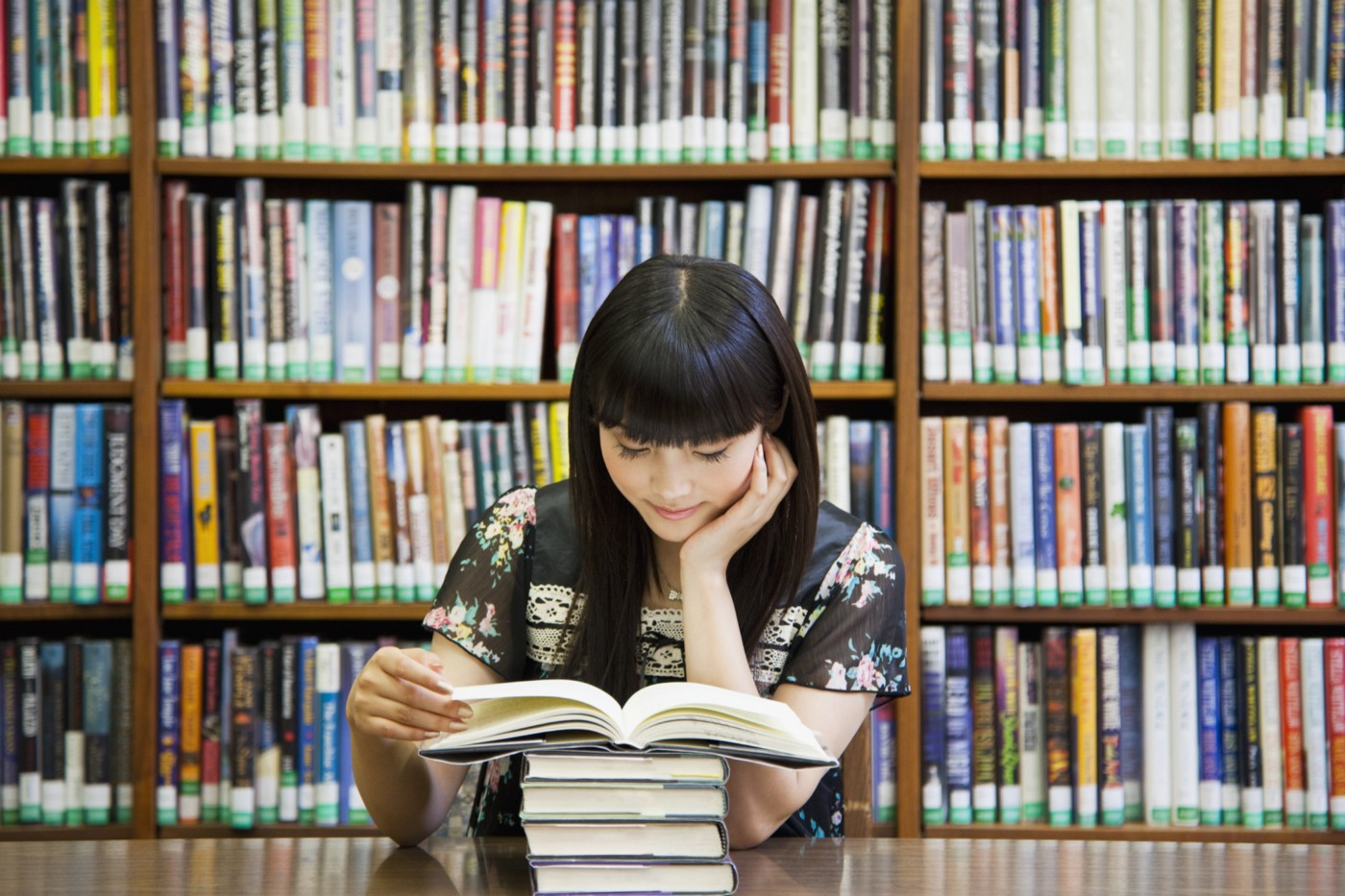 A photo of an Asian woman reading a book at a library.