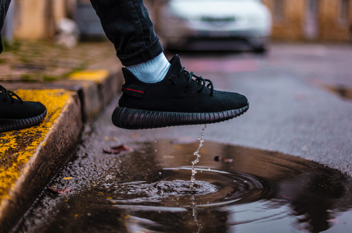 A person's foot (wearing a black sneaker) being lifted out of a puddle along a street.