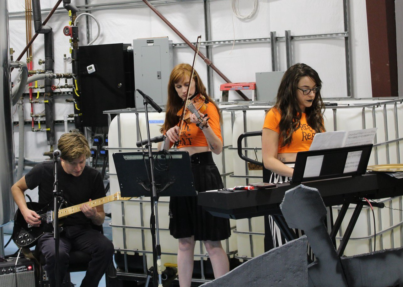 Patrick Chadwick playing guitar, Charley Daveler playing violin, and Anne Marie Wells playing electric keyboard