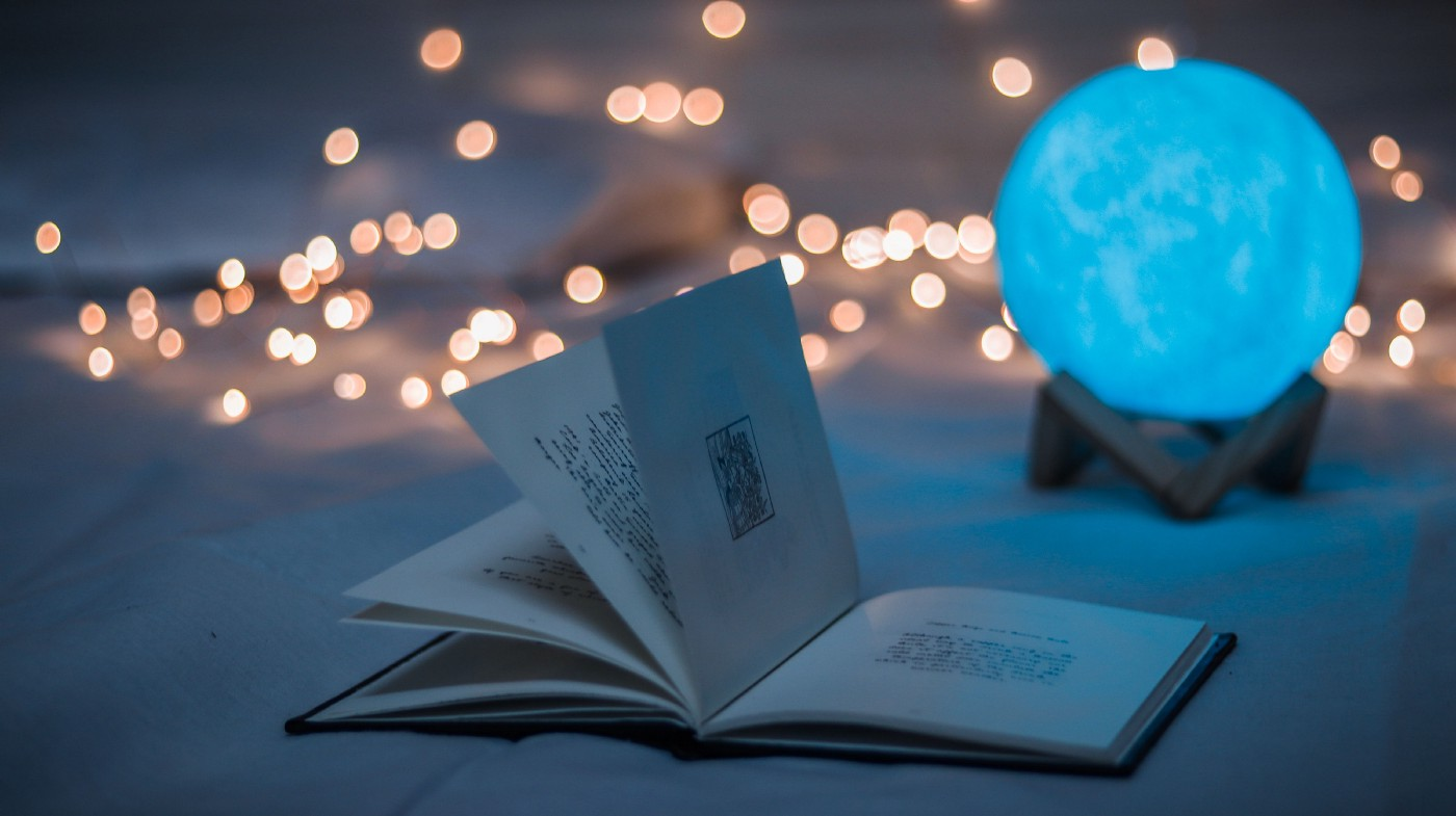 """A glowing blue orb and """"spell book"""" set against a faded background of atmospheric lights."""