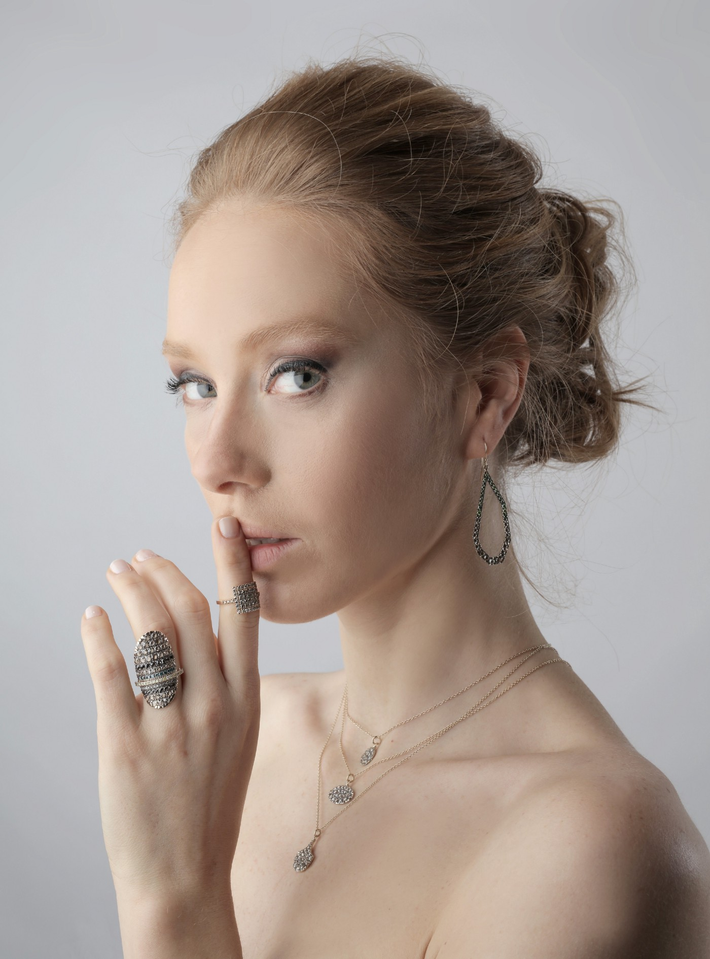 A woman suggestively holds a finger to her lips. Her hair is swept back in a messy bun. She wears rings and a necklace but the image suggests she is naked, though we only see above her breasts.