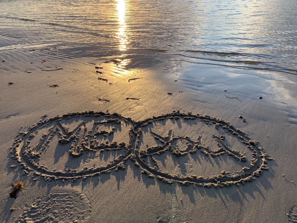 """The words """"Me"""" and """"You"""" with circles around them, written in sand on the beach."""