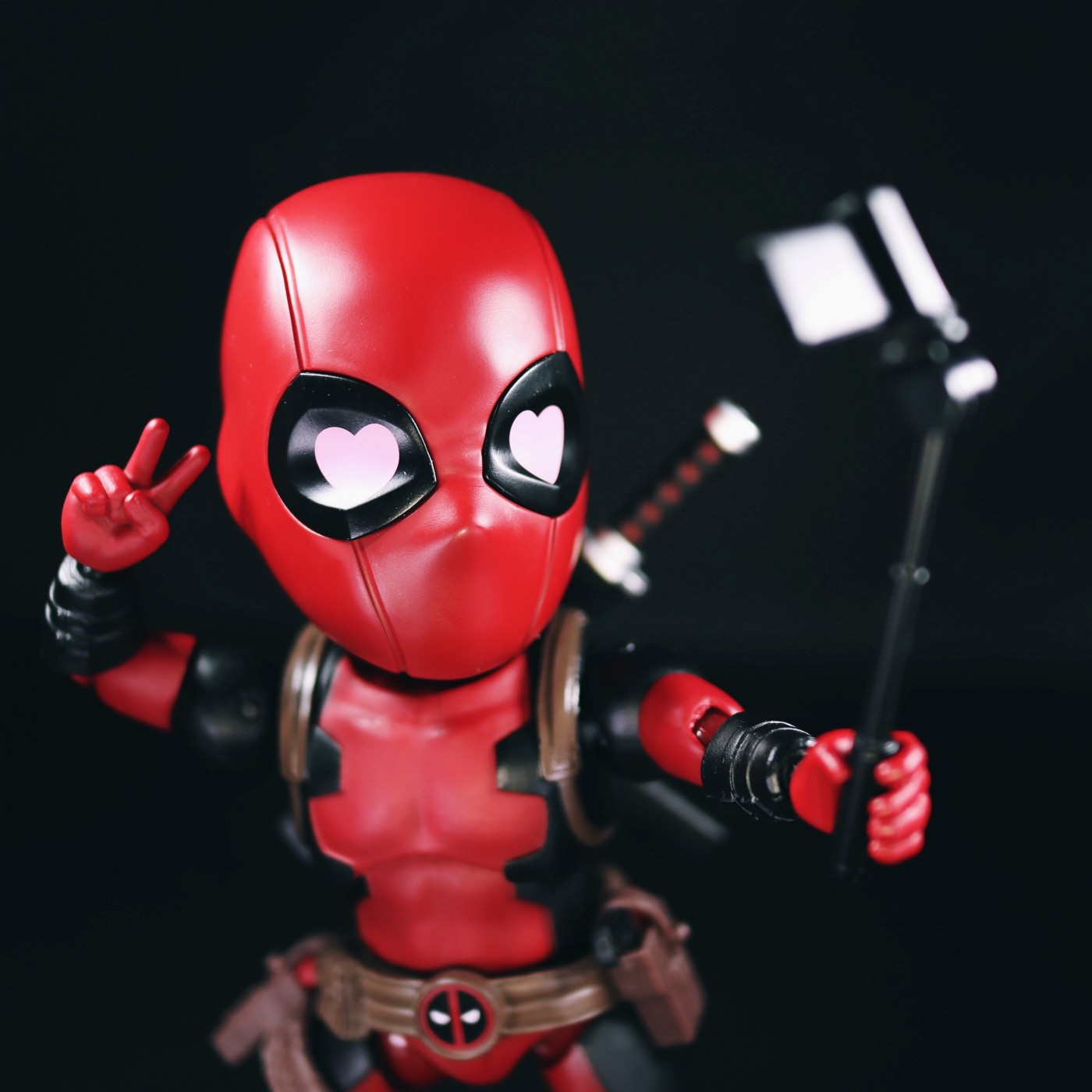 A photo of a toy doll of the superhero Dead Pool posing before his own smart phone on a selfie stick, throwing a peace sign with his free hand.