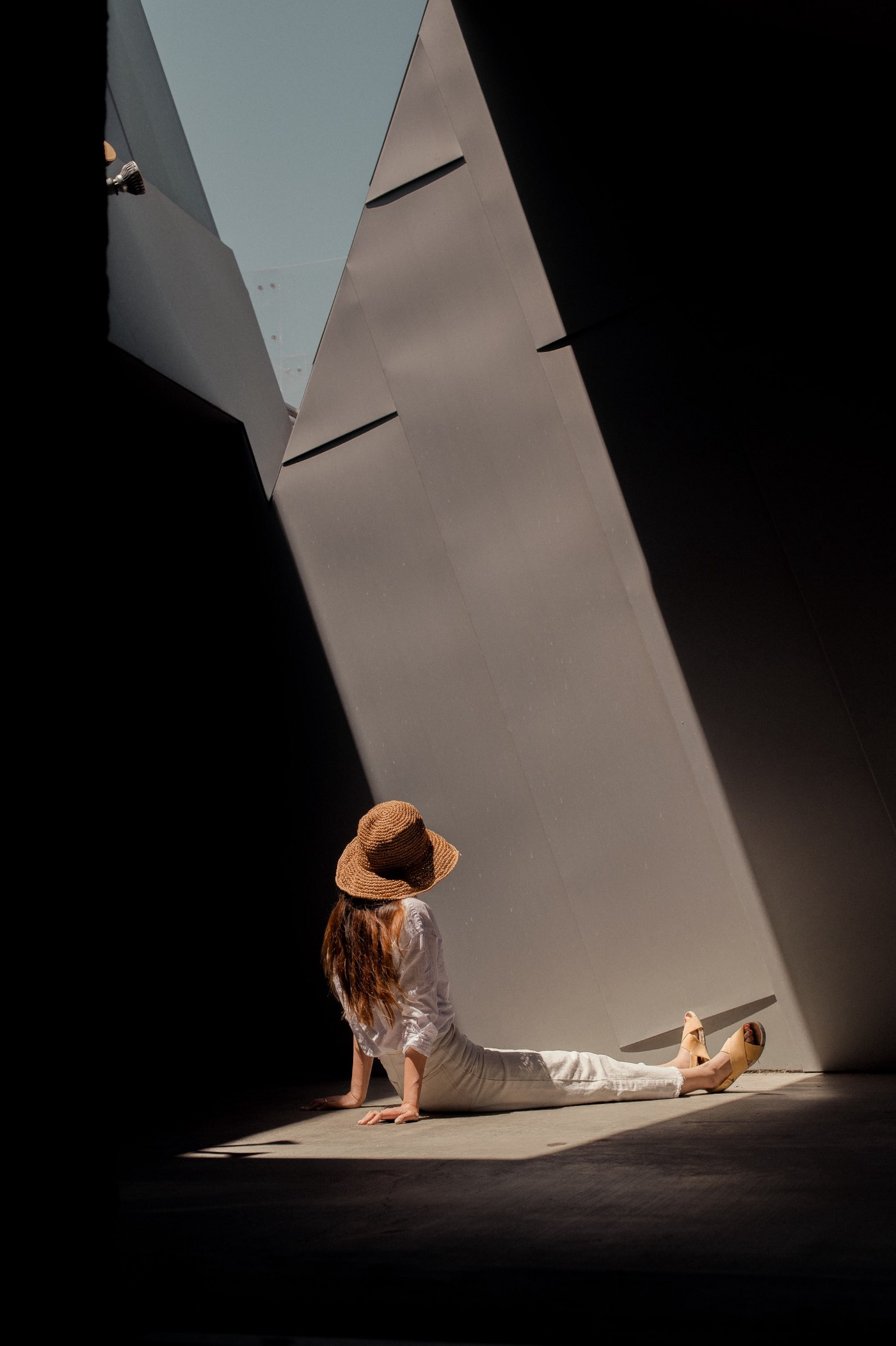 An image of a woman sitting in a building that appears to be post-modern architecture (an angular, dark building).