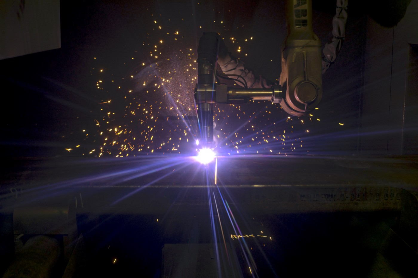 A robotic arm welding machinery as sparks fly around it.
