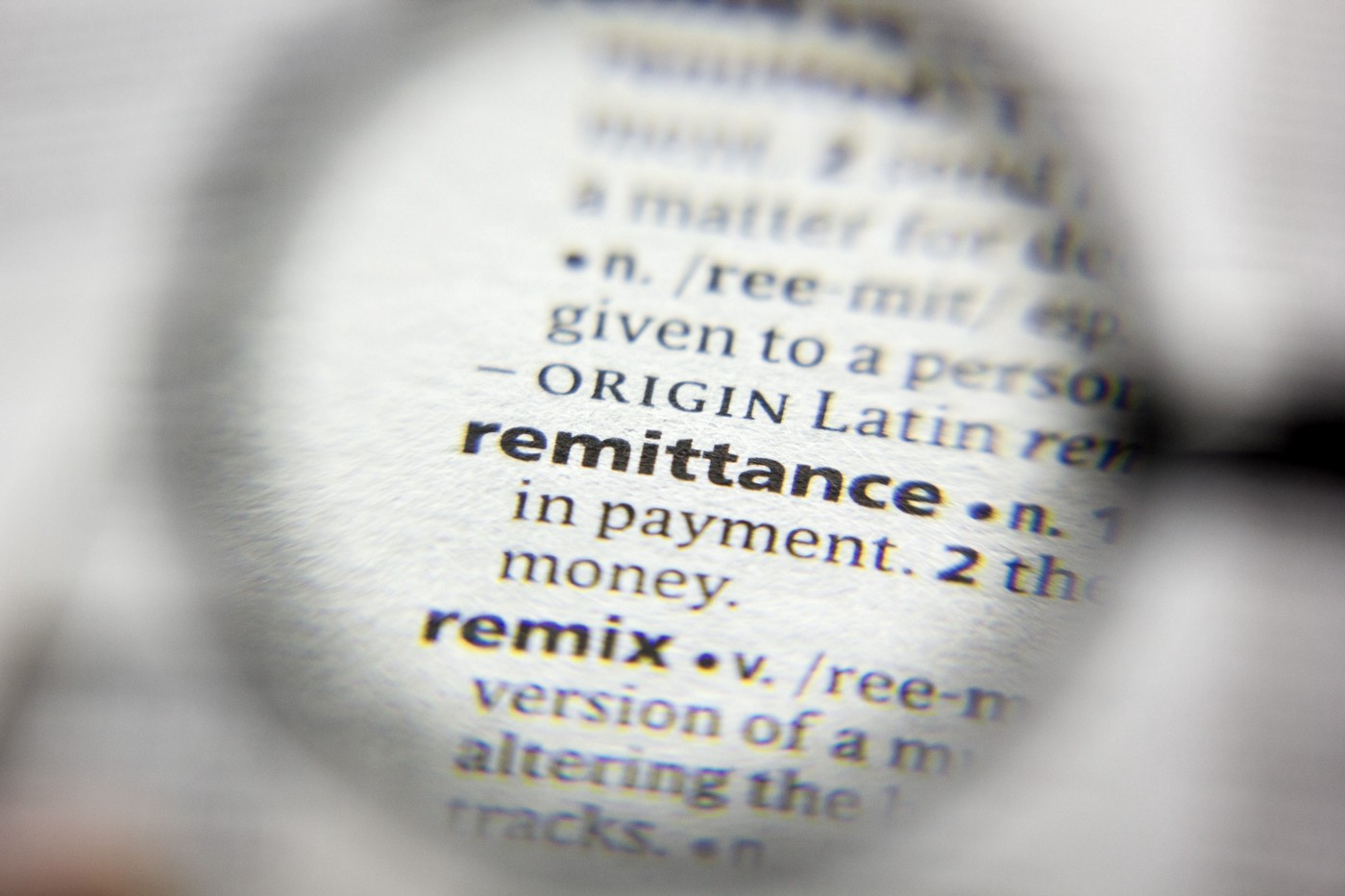 """The word """"remittance"""" under a magnifying glass."""