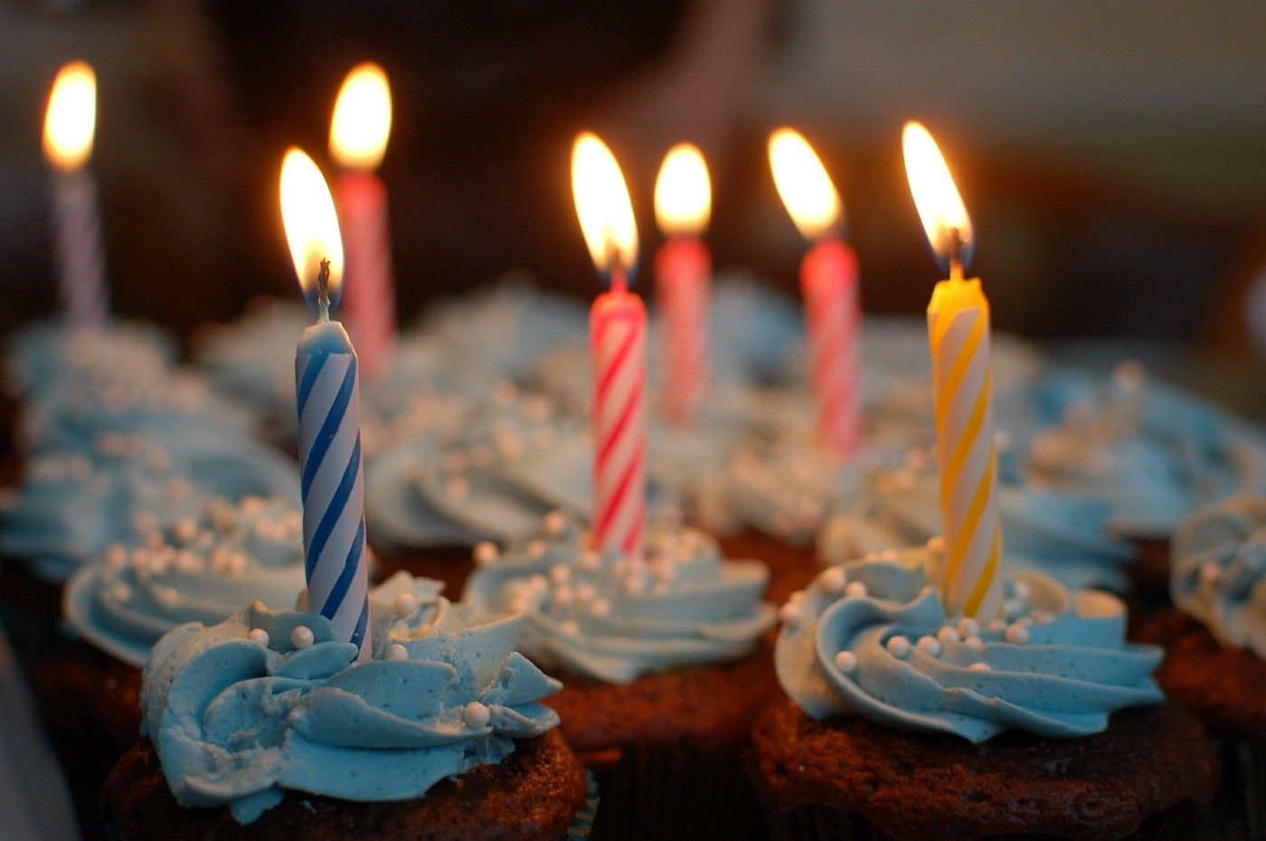 Cupcakes with blue swirled frosting and colourful lit birthday candles