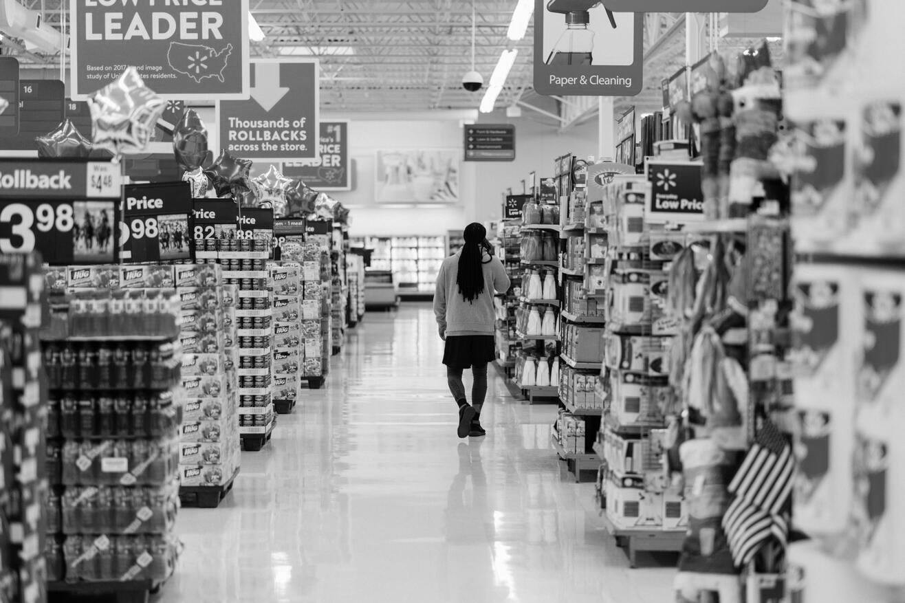 A black and white photo of an aisle/walkway at a supermarket with a woman with her back towards the camera placed in the background