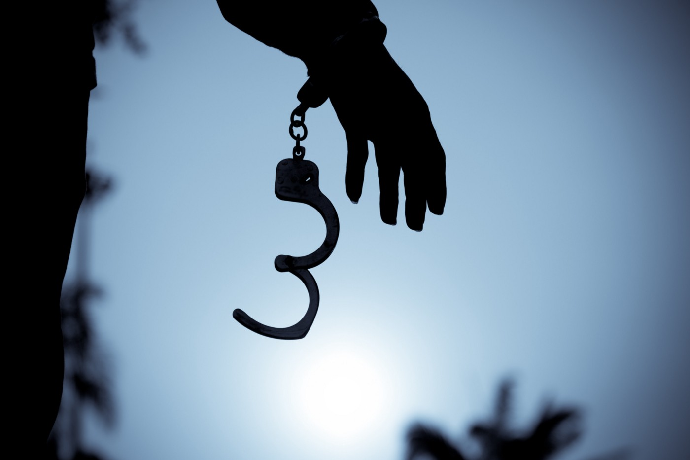A photo of handcuffs being uncuffed on a person's hand.