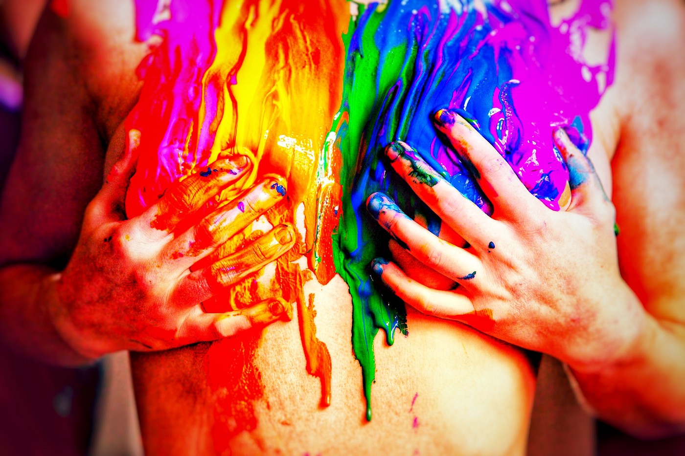 rainbow colors of paint slathered across the front of a naked person holding their breasts. Unknown if they are male or female