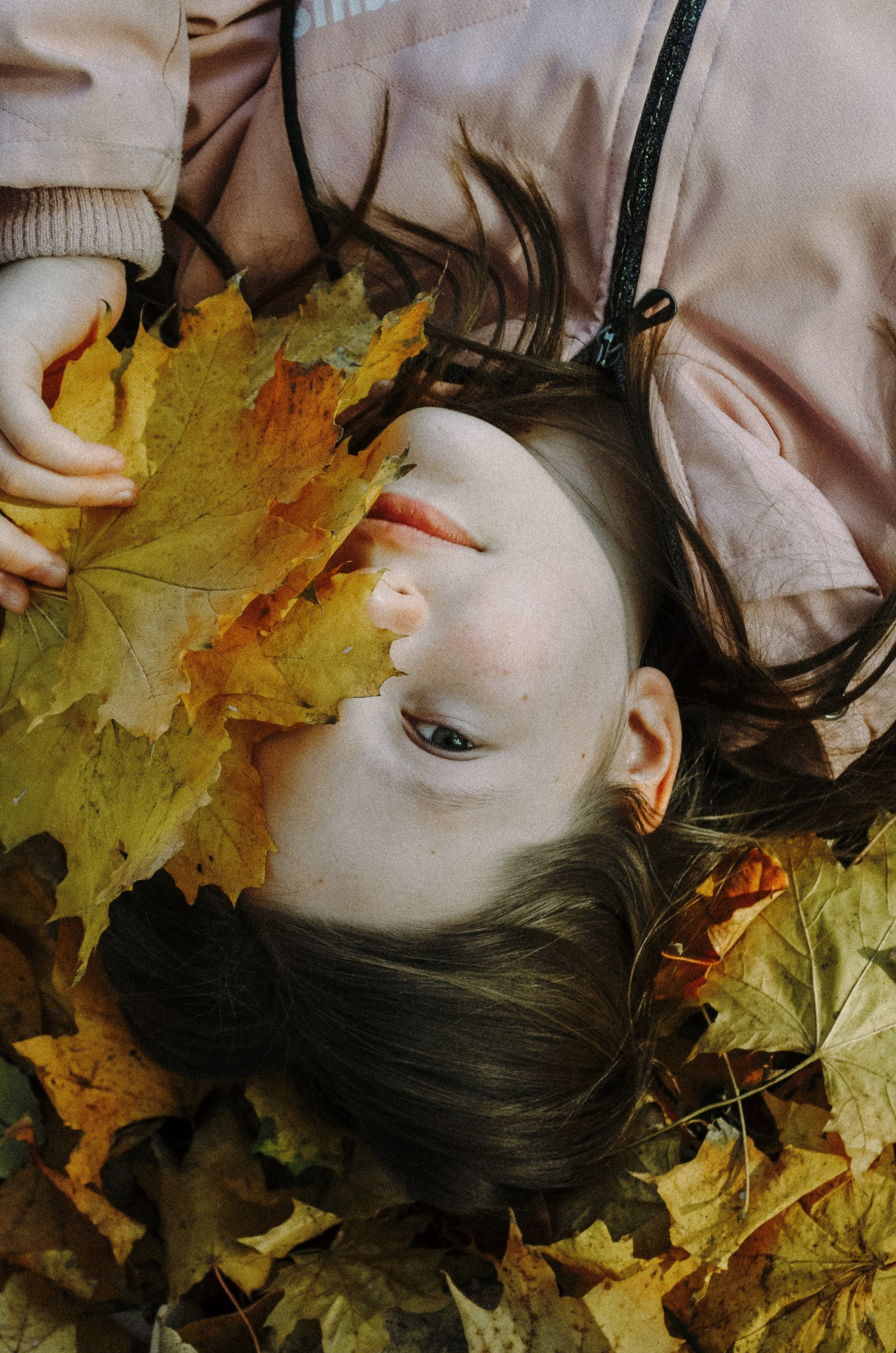 Woman laying on her back on the grass with a yellow and umber fall leaf covering half of her face. Calm and happy vibe.