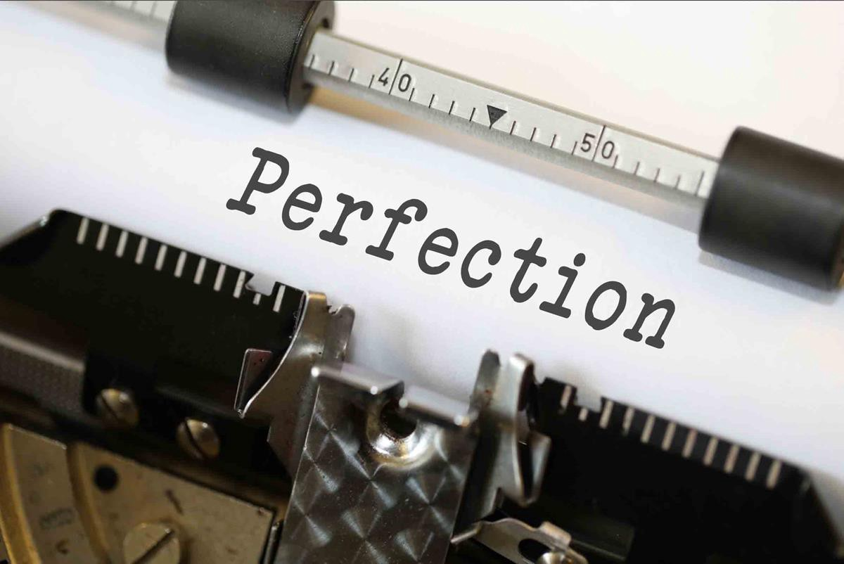 """Image is a closeup of an older typewriter that had a ribbon and keys that struck it. A page of white paper is in the roller with the one word """"Perfection"""" typed on it."""
