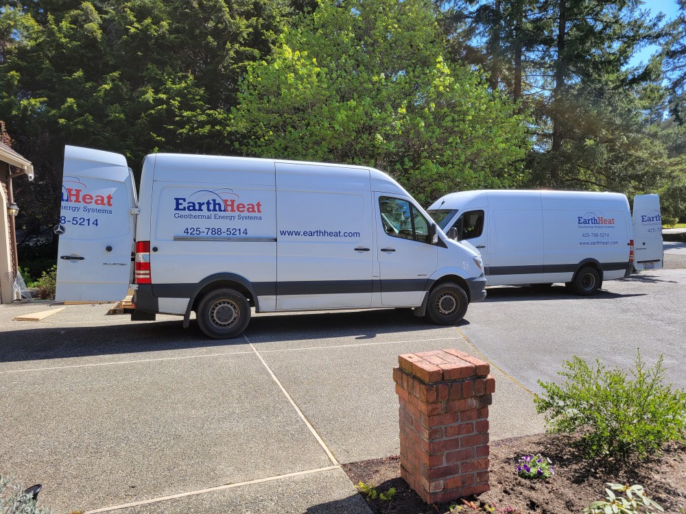 A pair of EarthHeat vans in the driveway during the inside installation work.