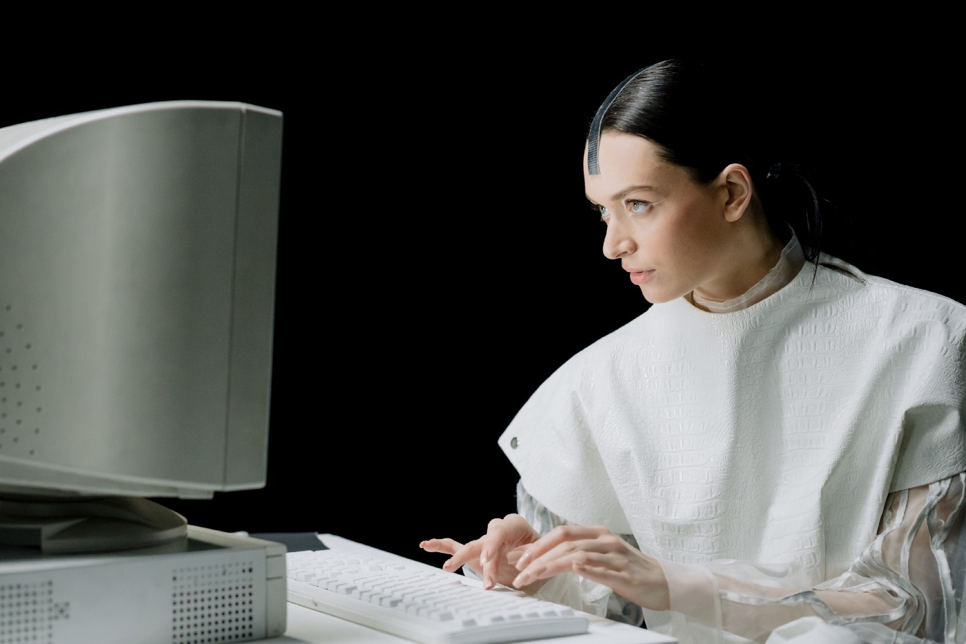 Woman in White Top Using an old Computer. Her clothing looks futuristic, and she looks like she's trying to hack into it. Kind of sly.