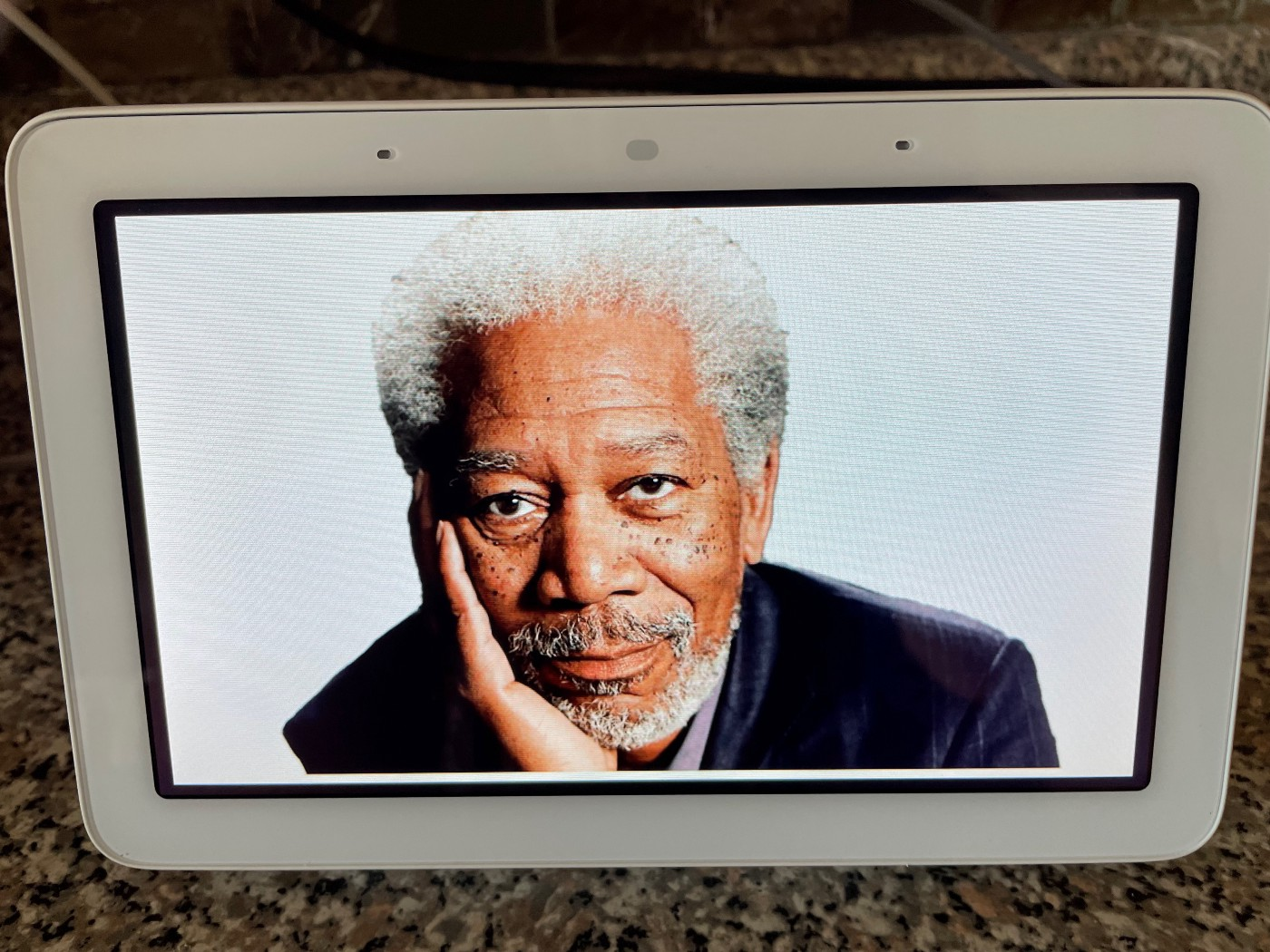 The face of American actor Morgan Freeman stares from within a Google Nest screen display on author Judy Millar's kitchen counter.