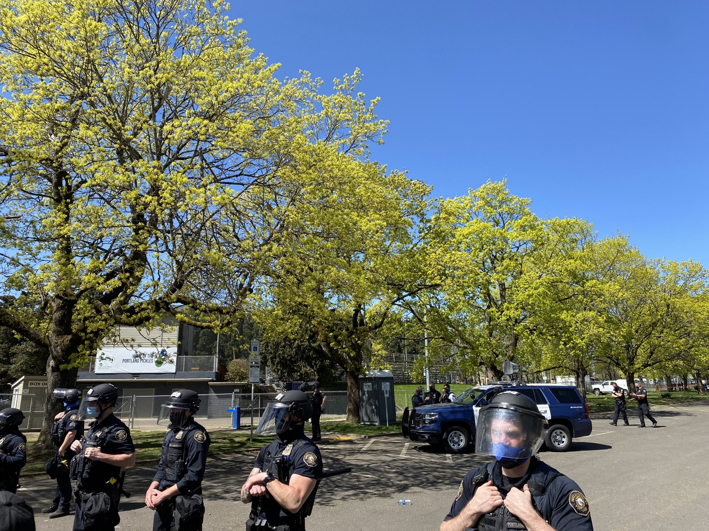 A line of police across the bottom of the photo. Behind them are a row of trees in Lents Park. A police SUV and more officers are visible in the background. Blue sky appears above the scene.