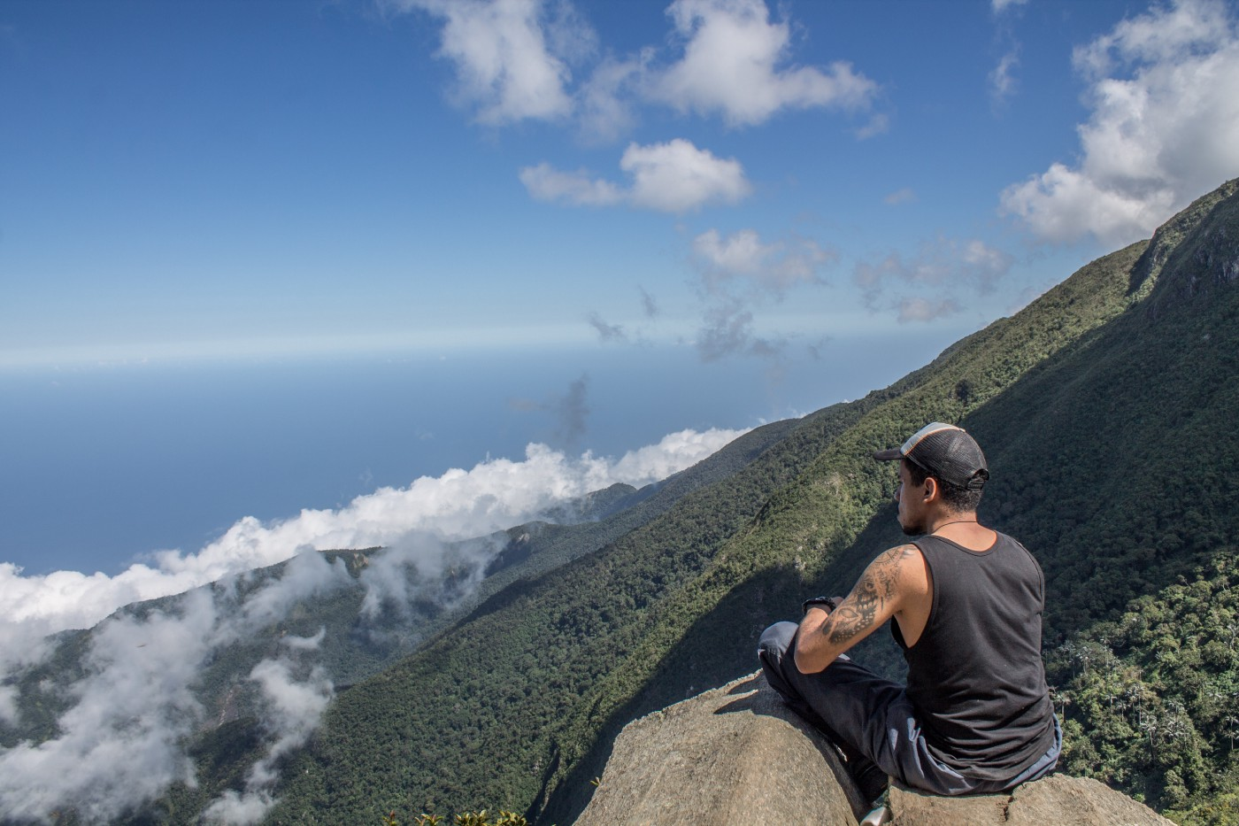 Photo of a man perched on a mountain looking out over an ocean.