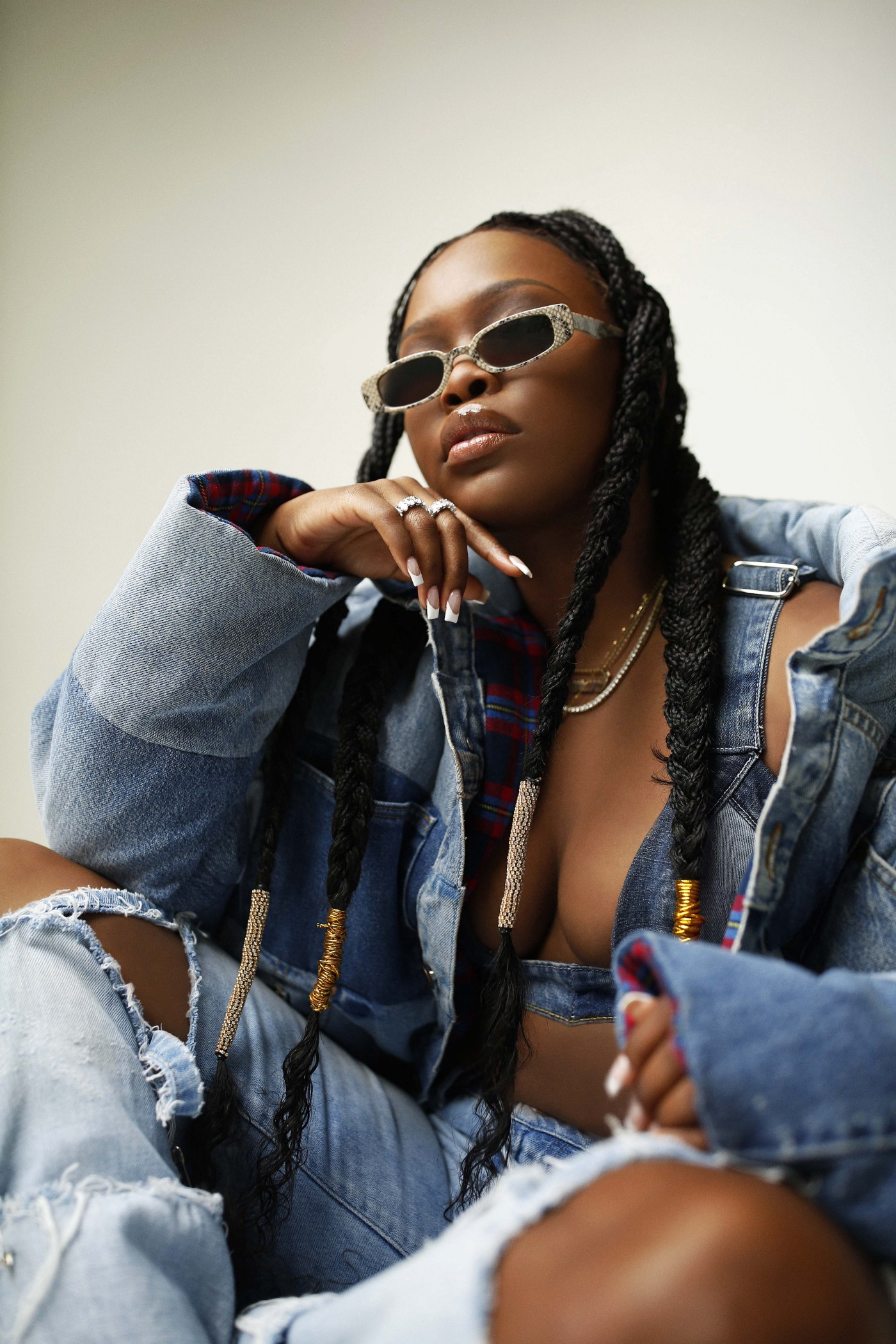 Stylish photo of Charm La'Donna wearing sunglasses and a cool denim outfit, taken from a lower angle.