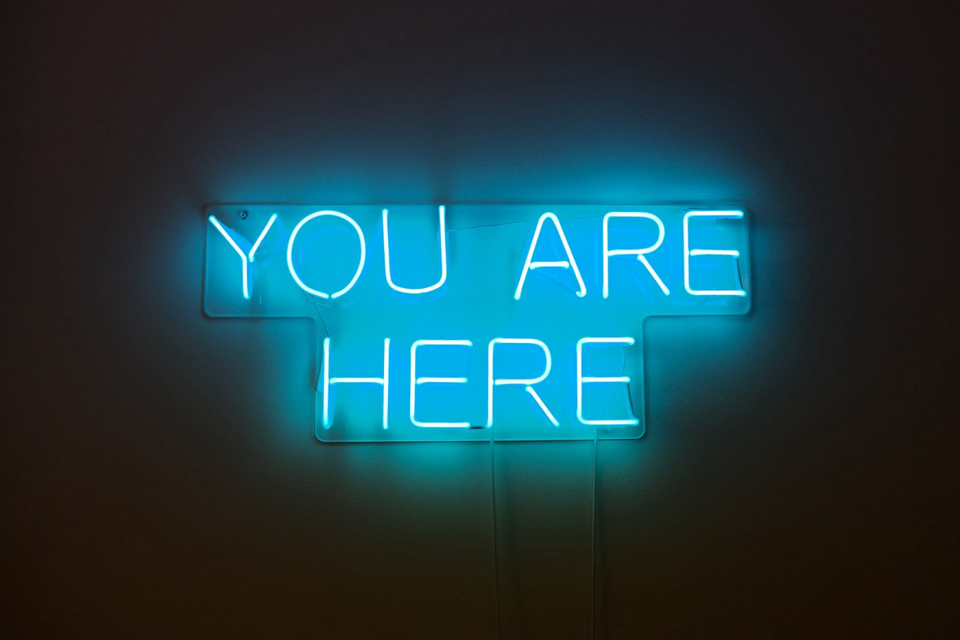 """A neon signs that says """"You are here"""""""
