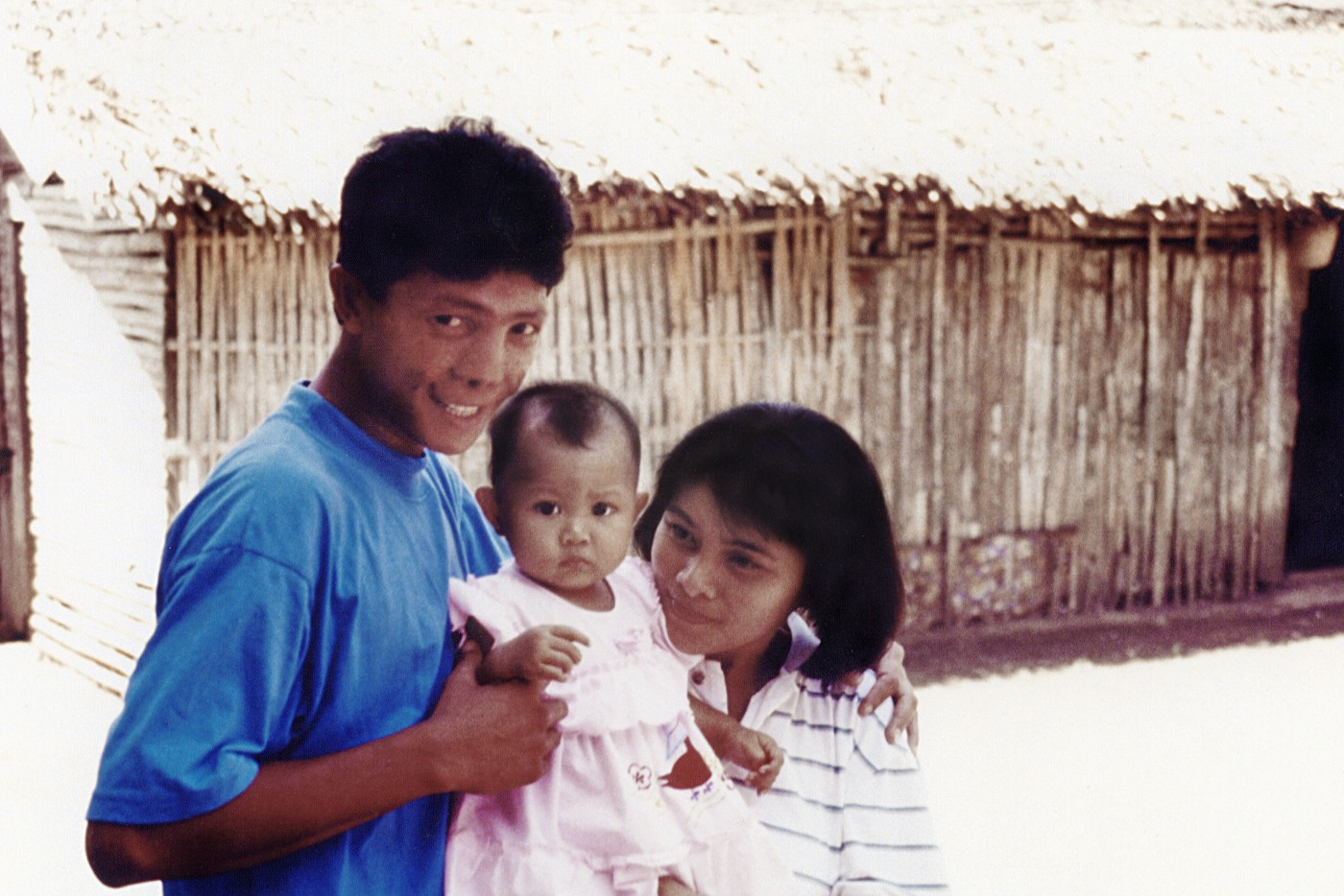 Antero poses with his child and wife after surgery outside of a building.