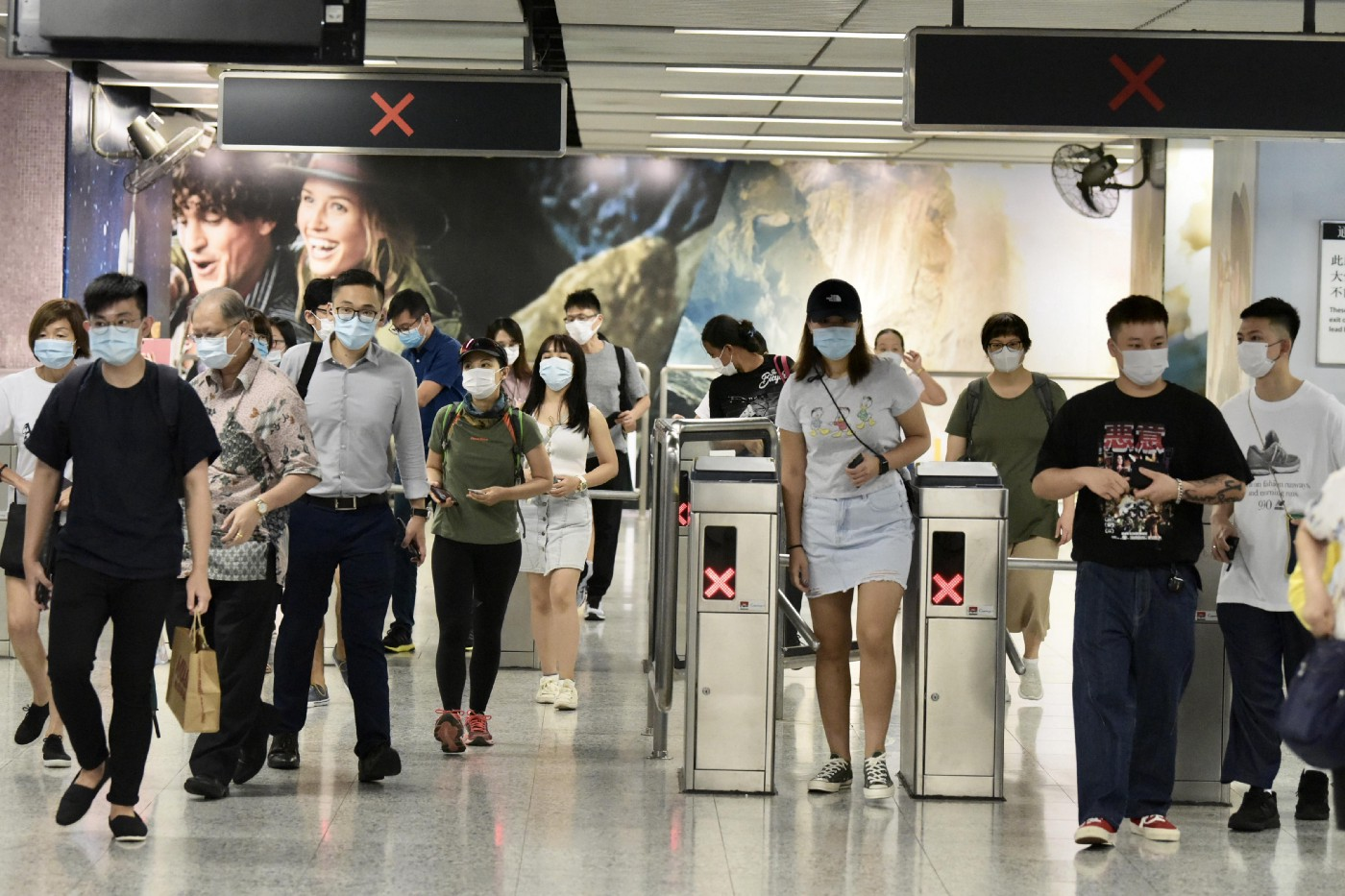 People wearing masks go through ticket barrier at the railway station in Hong Kong.