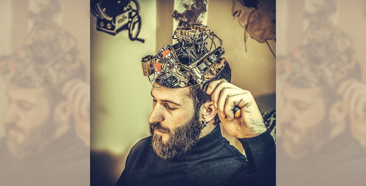 Bearded man in a black sweater with a car engine emerging from the top of his head, adjusting it with a screwdriver held in his left hand