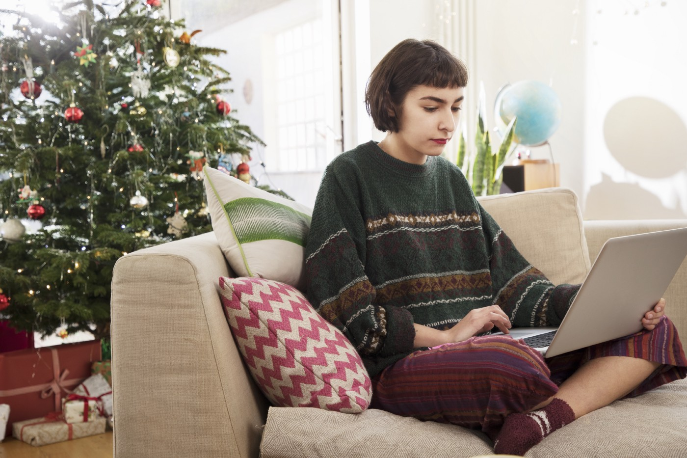 A person with short bobbed hair sitting on a couch in front of a Christmas tree, working on a laptop.
