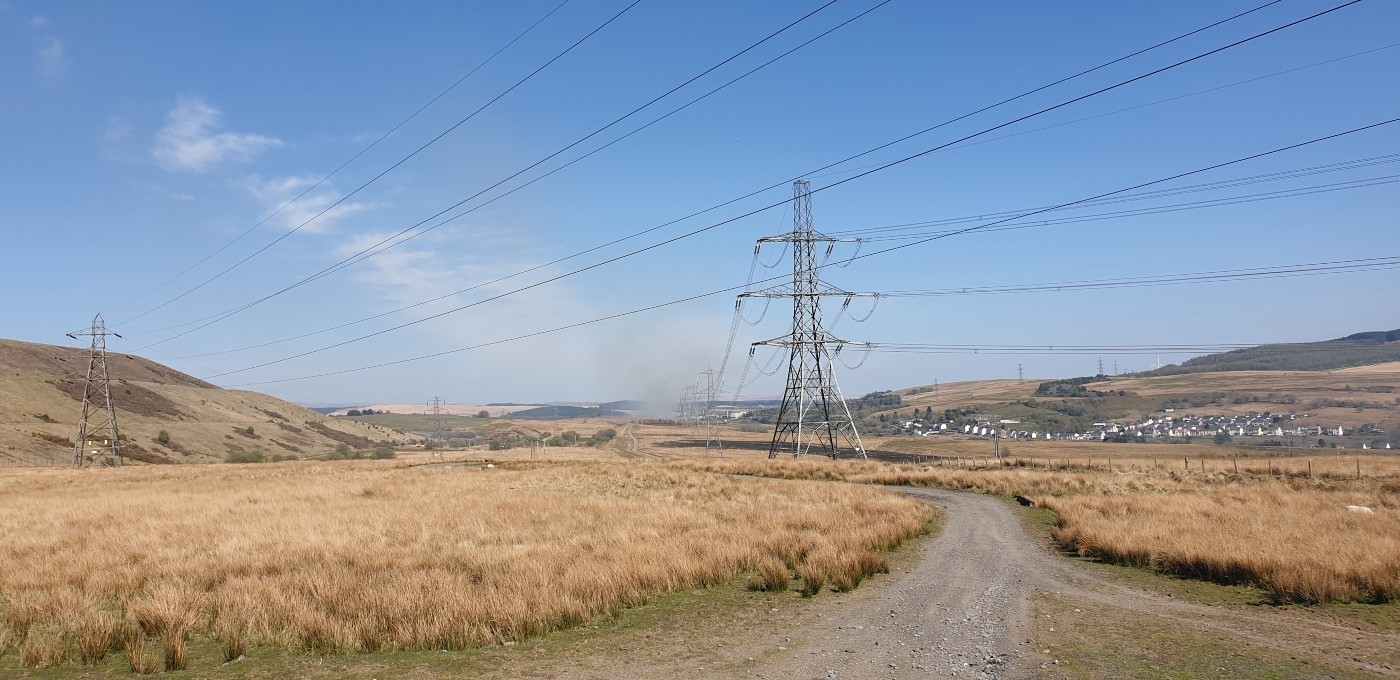 Power cables over fields of dry brown grass in the mountains, blue sky in the background