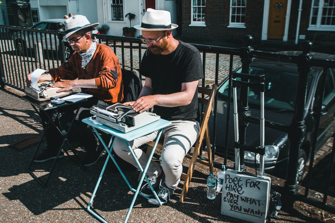 Two male poets, each with his own typewriter, sit side-by-side on a city street, writing poems for the public.