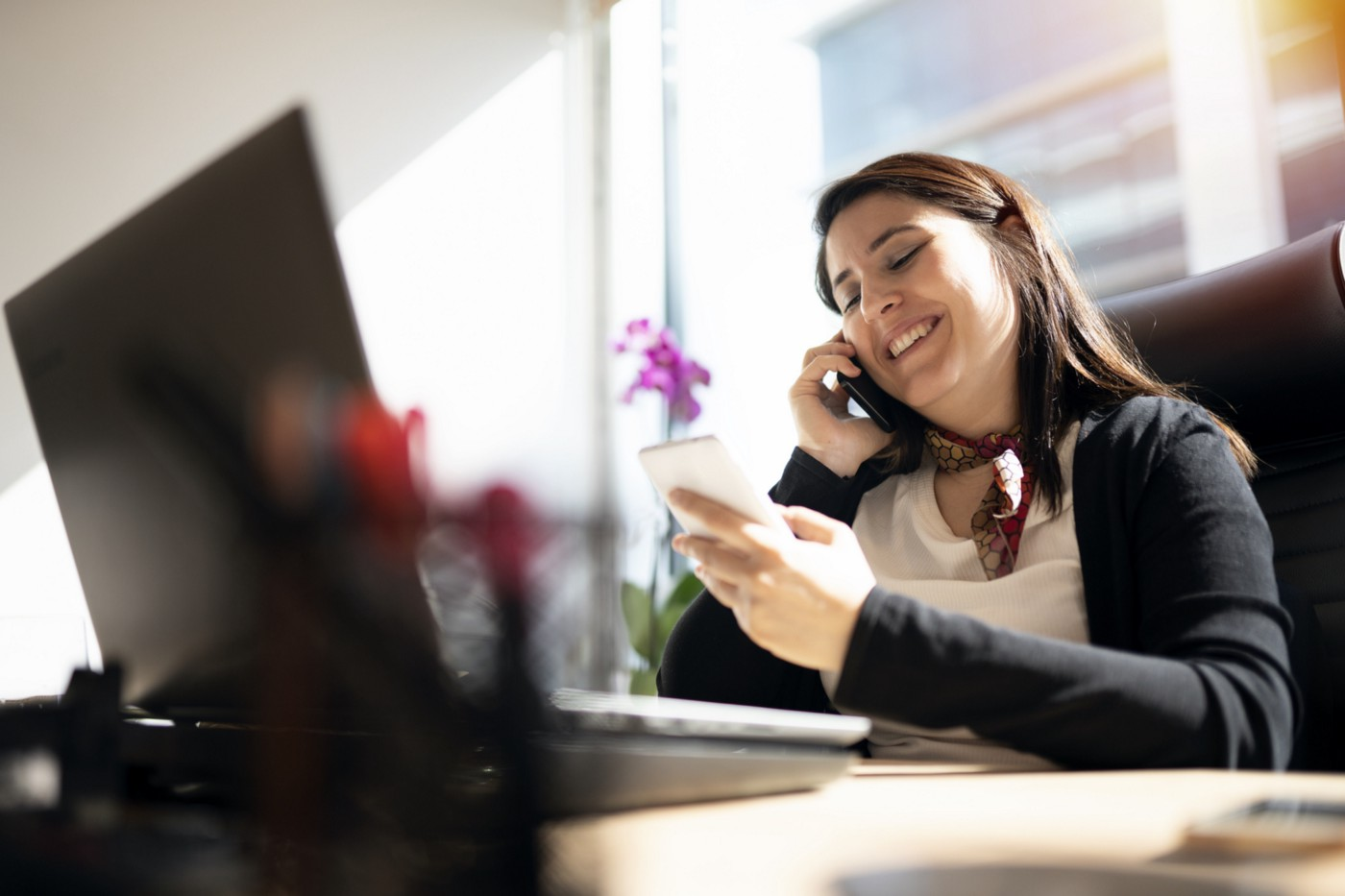 A photo of a smiling woman on the phone at her desk in front of her computer.