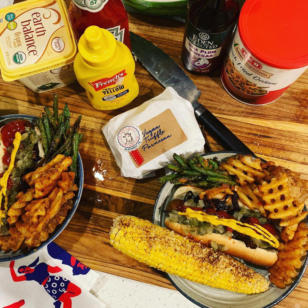 A plate piled with a hot dog, waffle fries, a seasoned corncob, and various vegan condiments.
