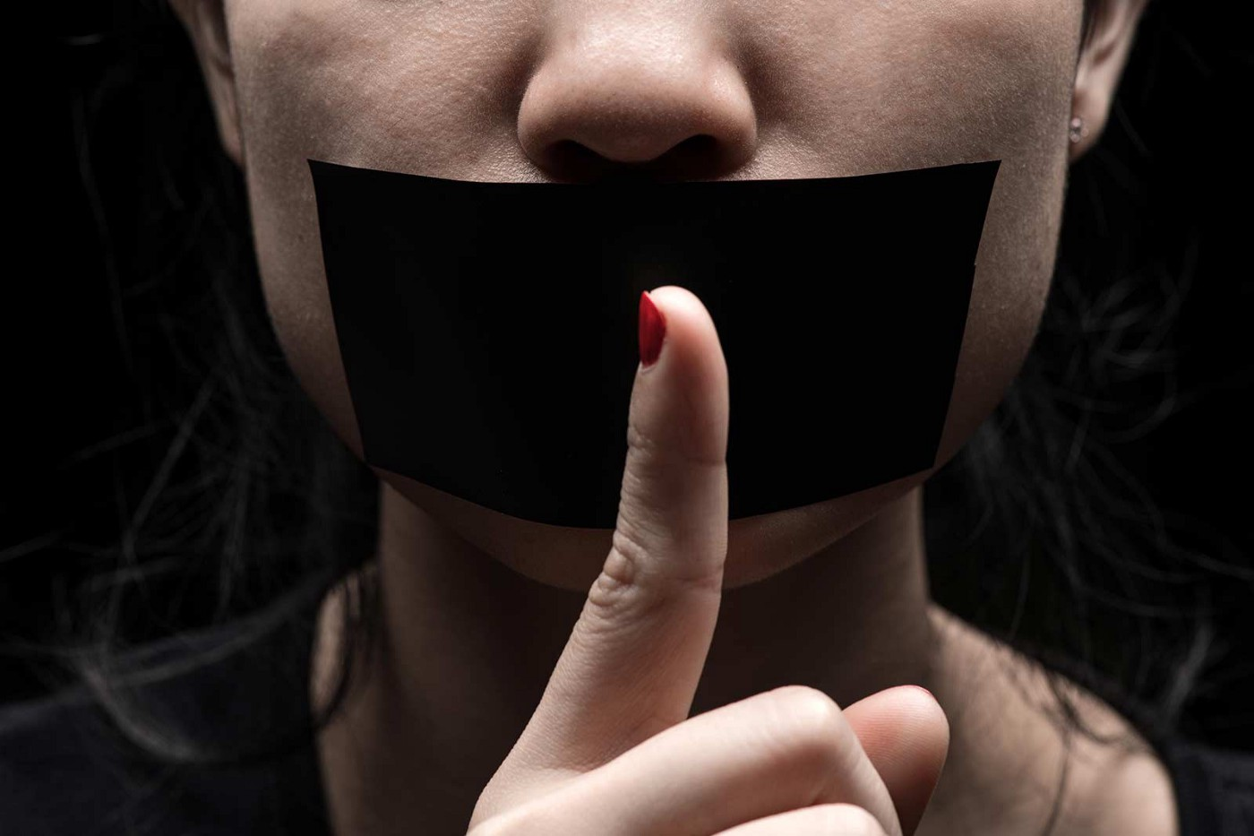 A woman has black tape over her mouth. She holds up a finger, telling us to be silent.