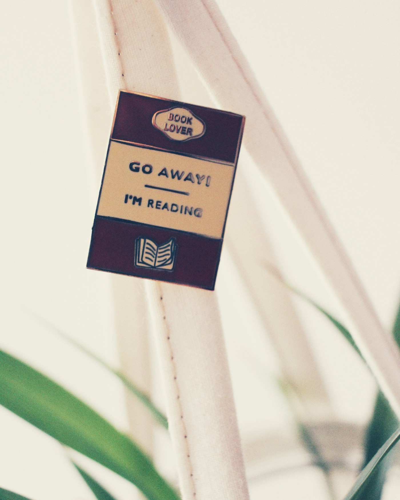 A small brown, tan metal pin with gold sans script text Go Away! I'm reading, is pinned to the strap of a muslin planter