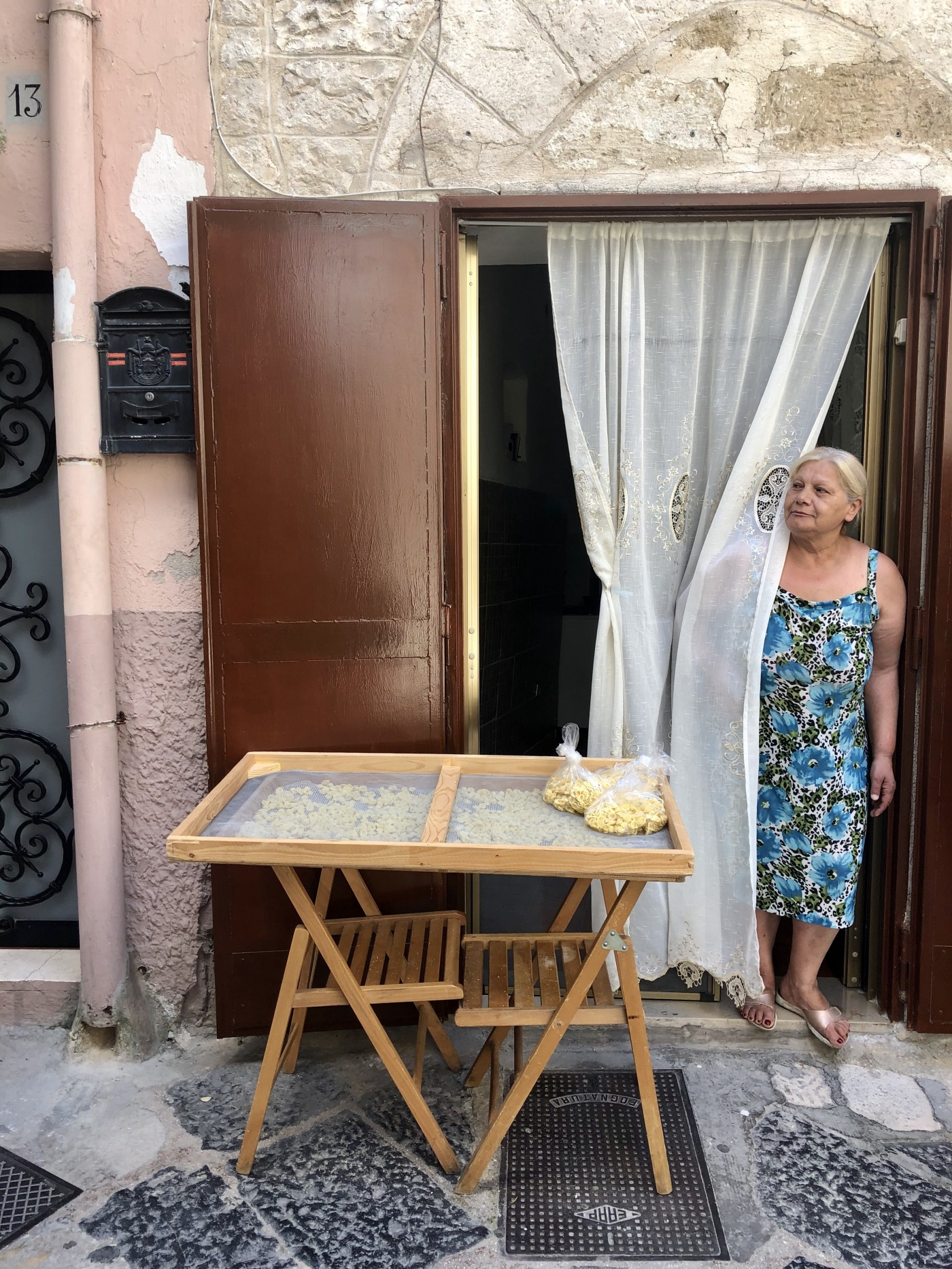 Pasqua, wearing a blue-and-green floral dress, peers around thin white curtains next to pasta laid out to dry outside.